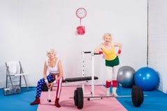 gelukkige sportieve hogere dames die in sportkleding bij camera glimlachen stock afbeeldingen