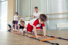 Gelukkige sportieve kinderen in gymnastiek stock fotografie