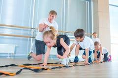 Gelukkige sportieve kinderen in gymnastiek Jonge geitjesoefeningen royalty-vrije stock foto