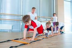 Gelukkige sportieve kinderen in gymnastiek Jonge geitjesoefeningen stock afbeelding