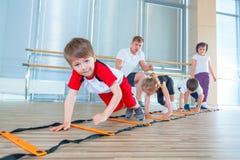 Gelukkige sportieve kinderen in gymnastiek Jonge geitjesoefeningen stock foto's