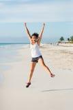 Gelukkige sportieve vrouw die bij Caraïbisch strand springen stock afbeelding