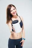 Gelukkige sportieve vrouw die kruik proteïne op camera geven royalty-vrije stock afbeelding
