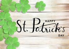 Gelukkige St Patrick de Typografieachtergrond van de Dag Zwarte Tekst met Groene Klavers op Houten Textuur stock fotografie