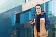 Gelukkige student die aan muziek op telefoon in openlucht luisteren De ruimte van het exemplaar stock afbeelding