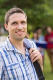 Gelukkige student die bij camera buiten op campus glimlachen Stock Foto's