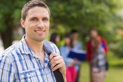 Gelukkige student die bij camera buiten op campus glimlachen Royalty-vrije Stock Afbeelding