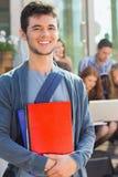 Gelukkige student die bij camera buiten op campus glimlachen Stock Foto
