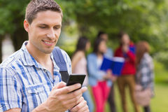 Gelukkige student die een tekst buiten op campus verzenden Stock Afbeelding