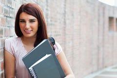 Gelukkige student die haar bindmiddelen houdt Stock Foto