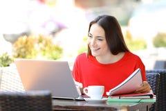 Gelukkige student die lezingsnota's bestuderen en laptop met behulp van royalty-vrije stock fotografie