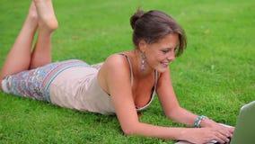 Gelukkige student die op gras liggen die haar laptop met behulp van stock video