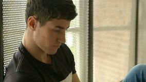 Gelukkige student die tablet gebruiken door het venster stock footage