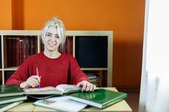Gelukkige student die terwijl het bestuderen en het bekijken camera glimlachen royalty-vrije stock afbeeldingen