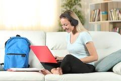 Gelukkige student e die gebruikend laptop en hoofdtelefoons leren royalty-vrije stock foto