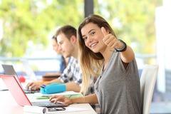 Gelukkige student met duimen omhoog in een klaslokaal royalty-vrije stock afbeeldingen