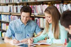 Gelukkige studenten die aan notitieboekjes in bibliotheek schrijven Royalty-vrije Stock Afbeeldingen
