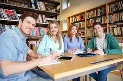 Gelukkige studenten die aan notitieboekjes in bibliotheek schrijven Stock Afbeelding