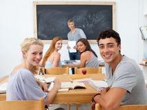 Gelukkige studenten die bij de camera glimlachen Stock Foto's
