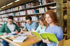 Gelukkige studenten die boeken in bibliotheek lezen Stock Foto's