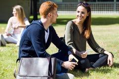 Gelukkige studenten die buiten op campus bij de universiteit zitten Royalty-vrije Stock Foto's
