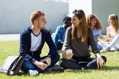 Gelukkige studenten die buiten op campus bij de universiteit zitten Royalty-vrije Stock Foto