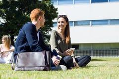 Gelukkige studenten die buiten op campus bij de universiteit zitten Stock Fotografie