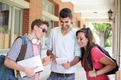 Gelukkige studenten die computer met behulp van Stock Foto's