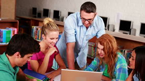 Gelukkige studenten die in de bibliotheek met hun privé-leraar samenwerken stock video