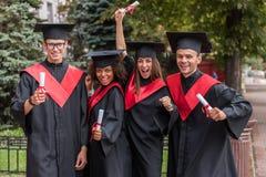 Gelukkige studenten die hun graduatie in traditionele kleren vieren royalty-vrije stock afbeeldingen