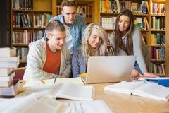 Gelukkige studenten die laptop met behulp van bij bureau in bibliotheek Royalty-vrije Stock Foto's
