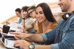 Gelukkige studenten die met gadget tijdens lezing onderhouden royalty-vrije stock fotografie