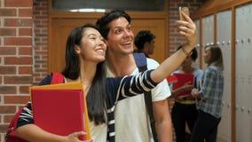 Gelukkige studenten die selfie in kleedkamer nemen stock videobeelden