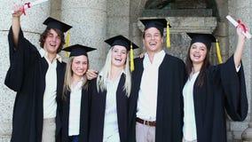 Gelukkige studenten die terwijl het houden van diploma's koesteren stock video