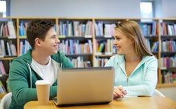 Gelukkige studenten met laptop in bibliotheek Stock Foto