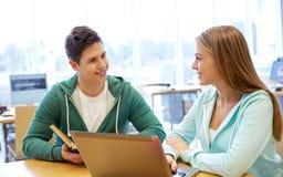 Gelukkige studenten met laptop en boeken bij bibliotheek Stock Foto