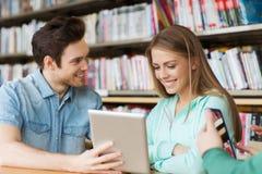 Gelukkige studenten met tabletpc in bibliotheek Stock Foto's