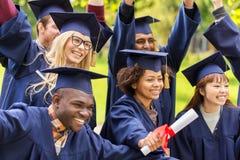 Gelukkige studenten in mortierraad met diploma's stock afbeeldingen