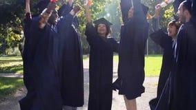 Gelukkige studenten in mortierraad met diploma's stock videobeelden