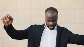 Gelukkige, succesvolle Afrikaanse Amerikaanse zakenman die geld werpen aan camera Geldregen, dalende dollars Langzame Motie stock videobeelden