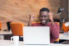 Gelukkige succesvolle Afrikaanse Amerikaanse zakenman in een modern startbureau binnen Stock Foto