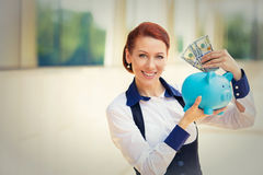 Gelukkige succesvolle jonge het bedrijfsvrouw deponeren gelddollars in spaarvarken Stock Foto