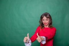 Gelukkige Succesvolle mooie vrouw in modieuze rode kleding die duim op symbool tonen door twee handen Geïsoleerdc op groene achte royalty-vrije stock fotografie