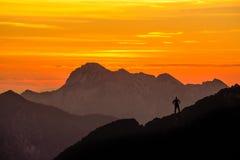 Gelukkige succesvolle winnende mens die bergtop bereiken Spectaculaire gelaagde bergketenssilhouetten met sinaasappel stock afbeelding
