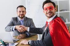gelukkige super zakenman in masker en kaap het schudden handen met zakenman stock foto