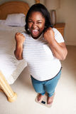 Gelukkige Te zware Vrouw die zich op Schalen in Slaapkamer bevinden Stock Foto