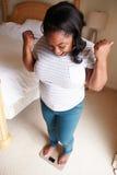 Gelukkige Te zware Vrouw die zich op Schalen in Slaapkamer bevinden Stock Afbeeldingen