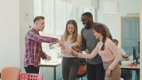 Gelukkige team het drinken alcohol in werkplaats Jonge mens het openen fles champagne stock videobeelden