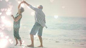 Gelukkige teruggetrokken oudsten die op het strand met hartenanimatie voor valentijnskaartdag dansen stock footage