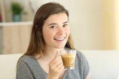 Gelukkige tiener die een koffie met melk houden die u bekijken stock foto